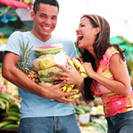 A photo of a man holding a armful of different fruits, while a woman laughs as she adds more to his armful